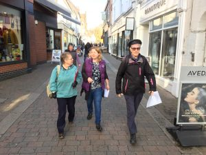 A picture of three people holding sheets of paper, ready to interview people in the town of Loughborough
